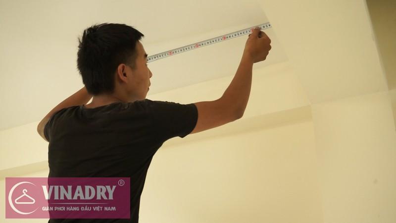 Thợ kỹ thuật đo trần bê tông để xác định các điểm lắp puli dẫn hướng và điều hướng giàn phơi.